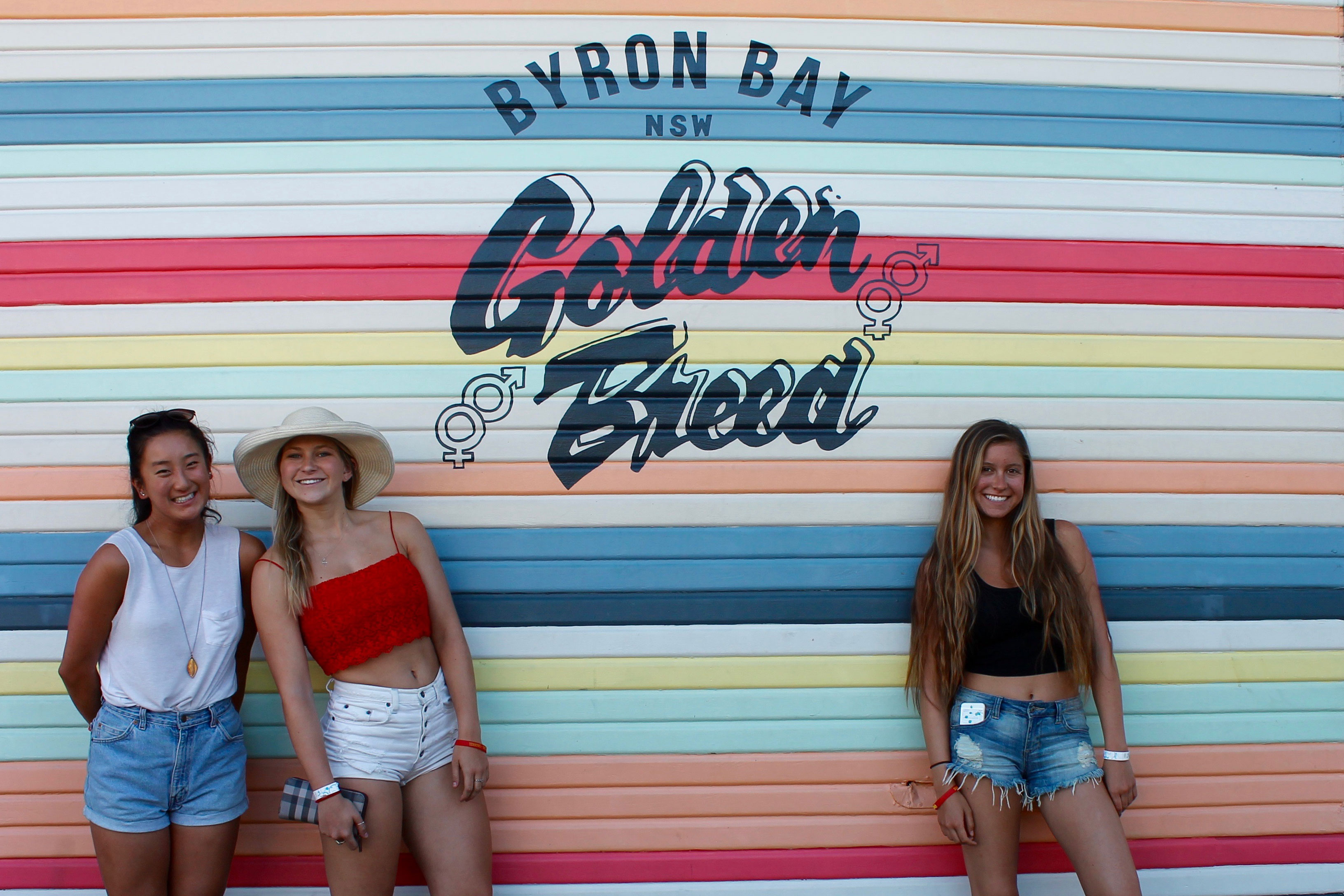 Girls smiling in front of a mural