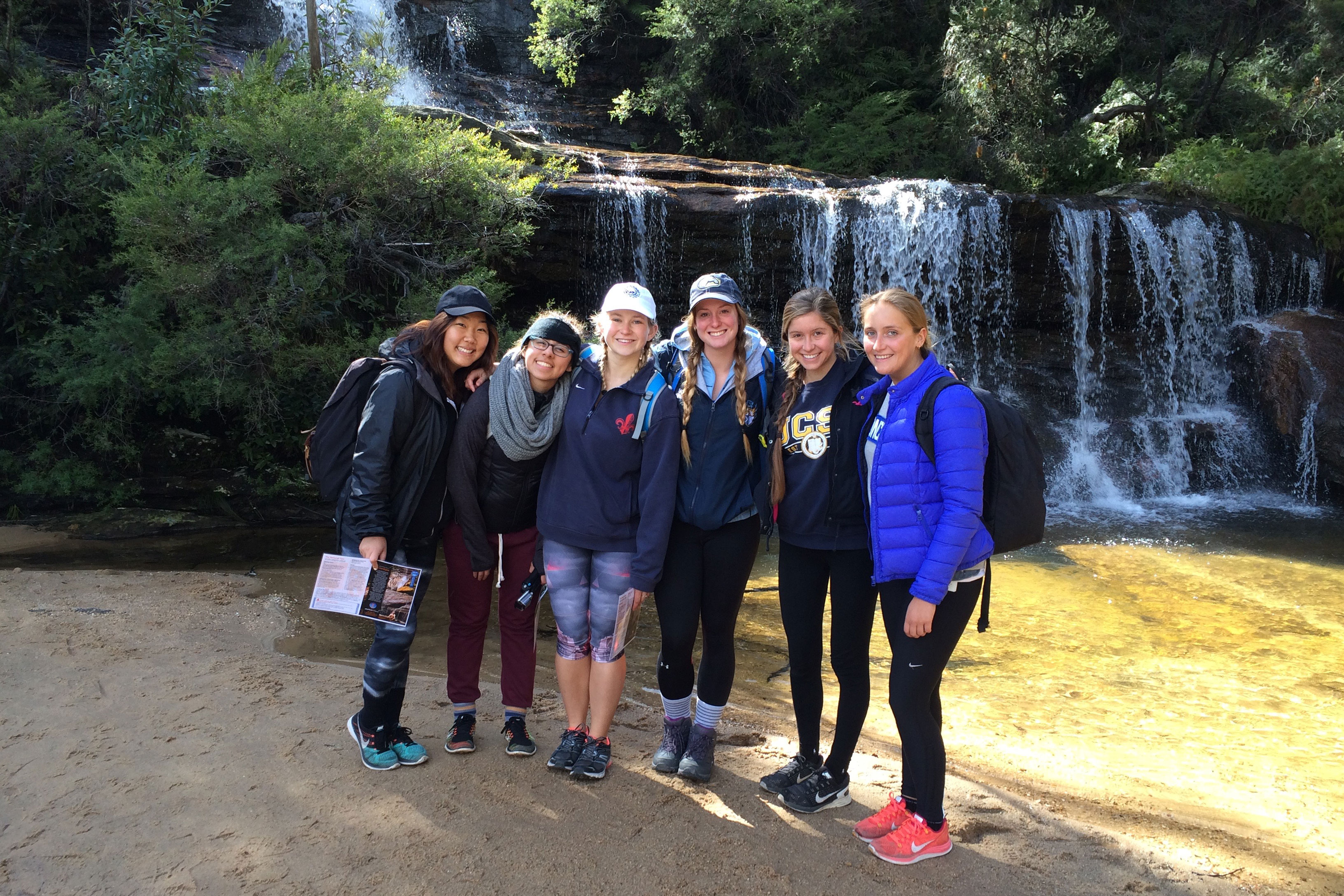 Group of friends posing in front of a waterfall