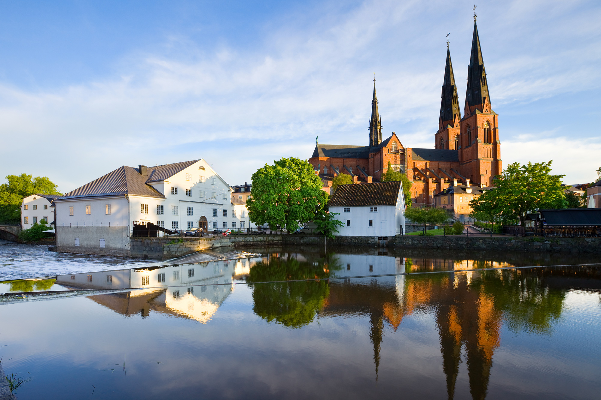 Traditional houses and the Cathedral reflecting in the Fyris river (Fyrisan) in Uppsala, Sweden
