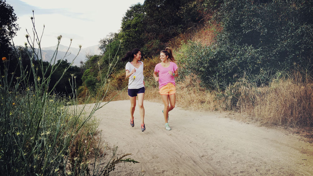 Two college students running on a dirt trail