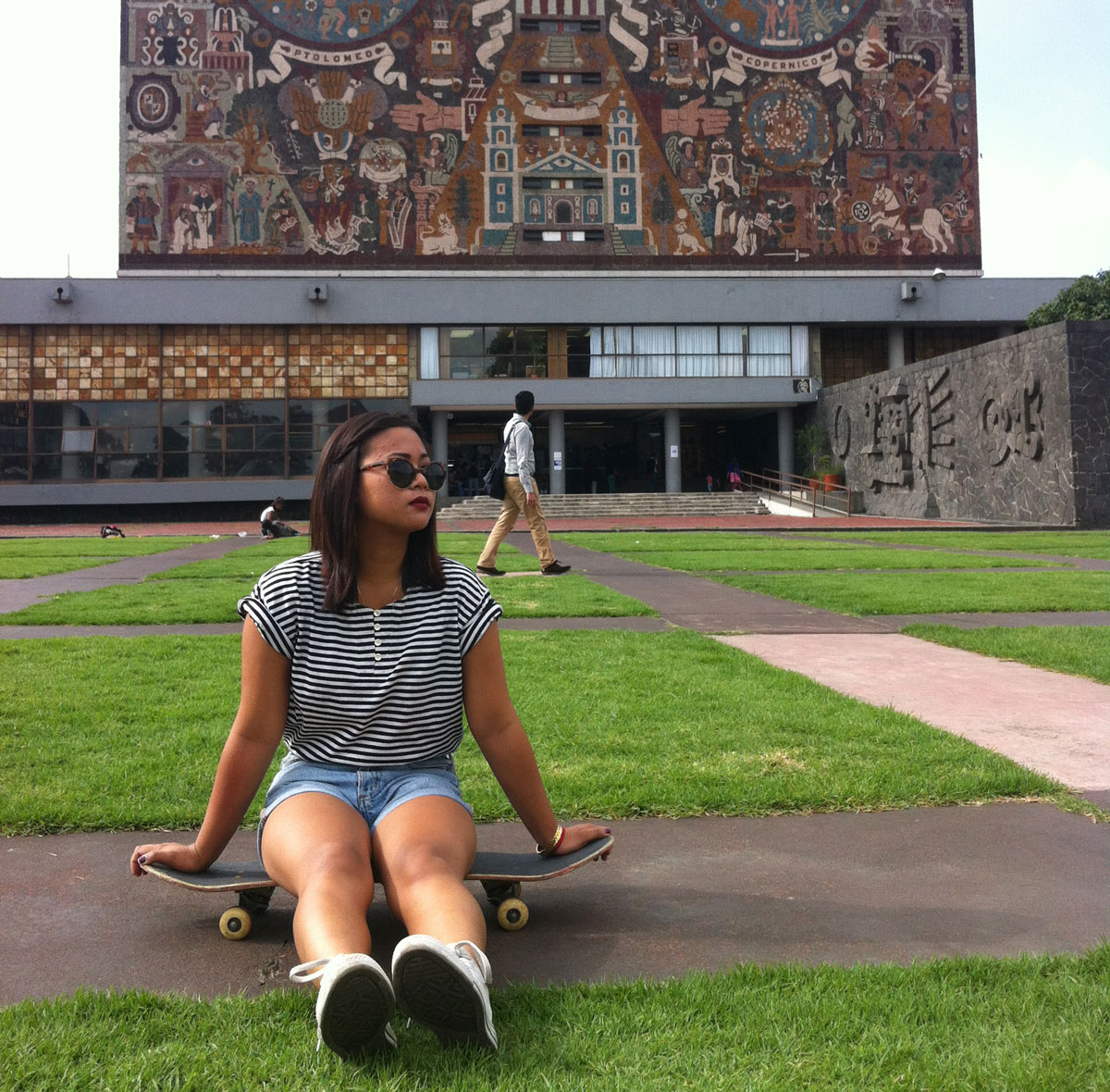 Photo of a UC student on a skateboard in front of a university building in Mexico