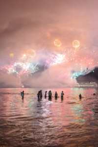 Silhouettes of people in the water with fireworks in the sky