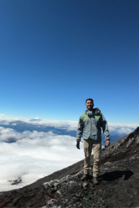 Ricardo standing on a mountain overlooking the clouds