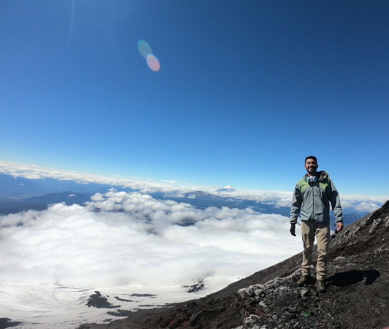 Ricardo standing on the top of a mountain with a beautiful landscape and clouds behind him