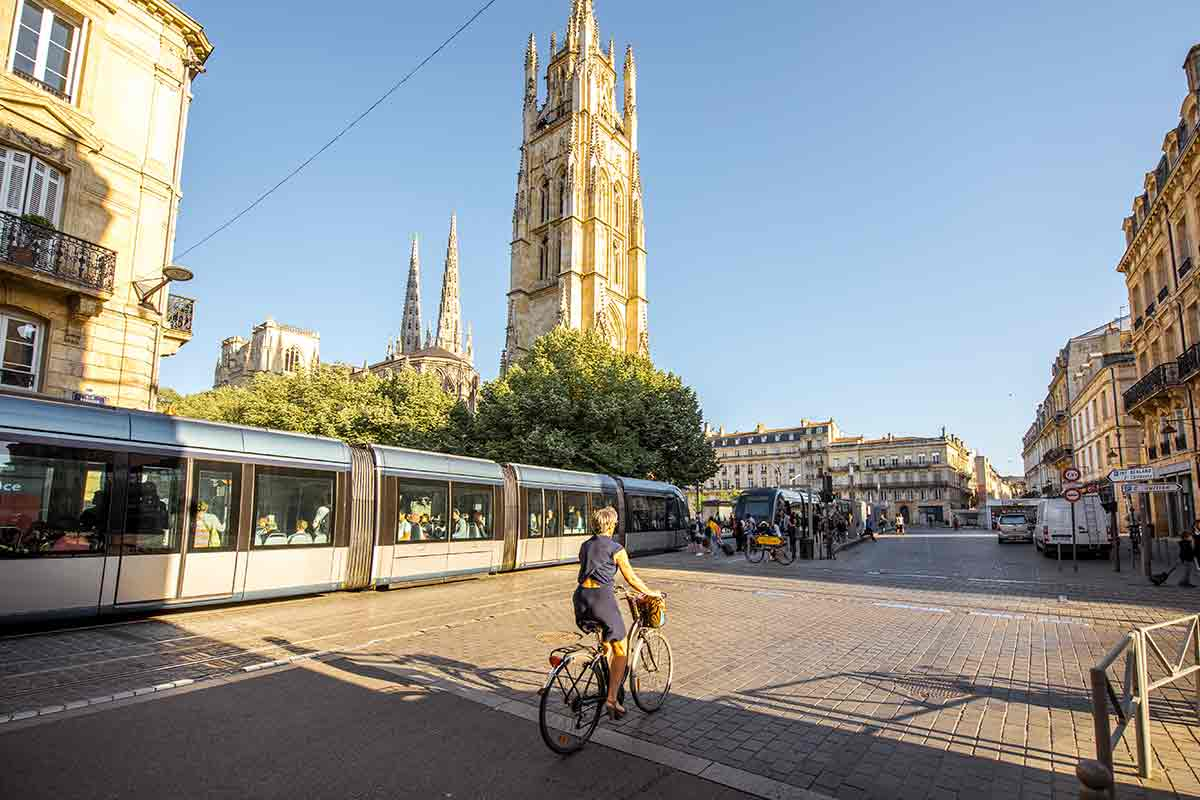 Bordeaux Cathedral with train and woman biking past