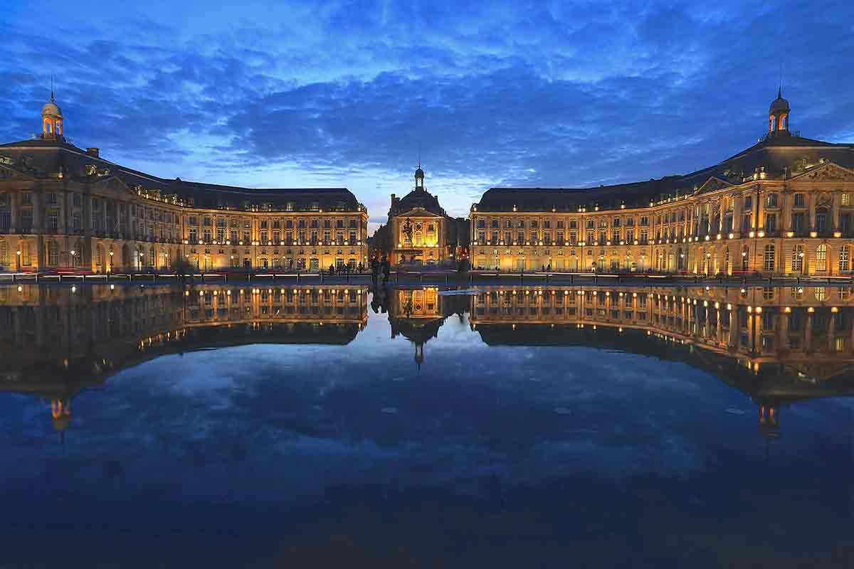 Plaza with mirror pool in Bordeaux at night