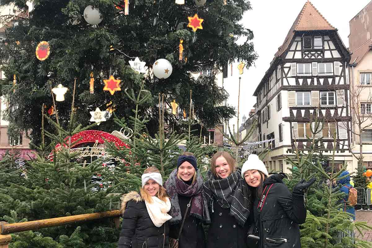Tracie with three friends smiling in front of a decorated Christmas tree