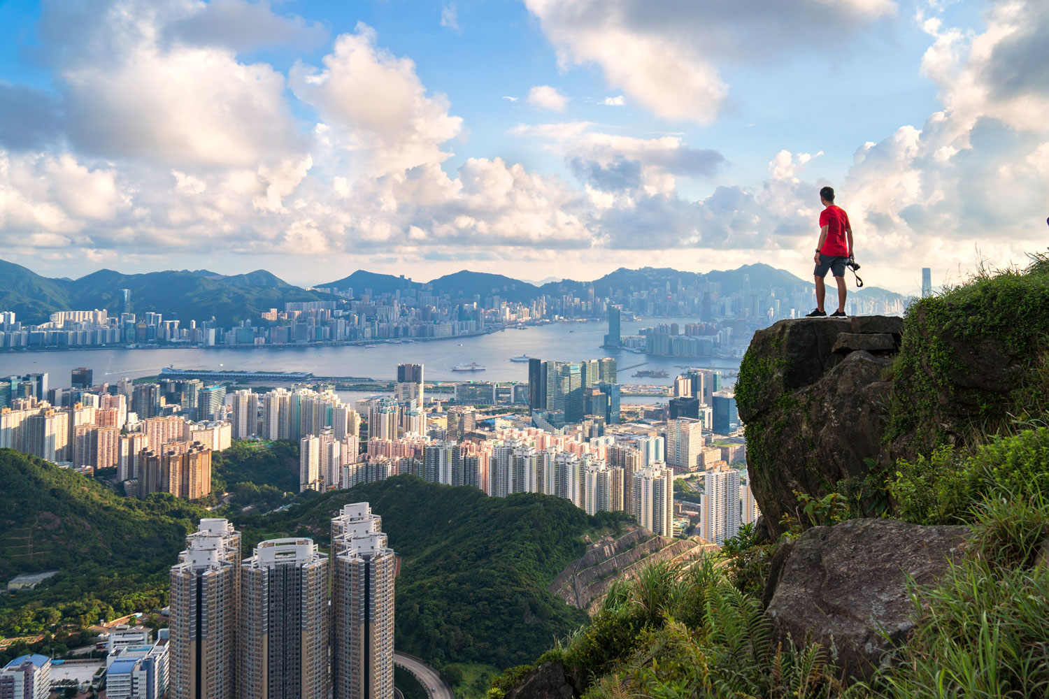 Cityscape of Hong Kong with a photographer looking down from lookout spot.
