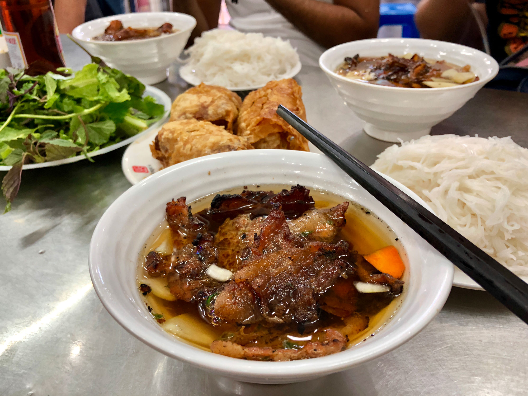 Bun Cha in a bowl with other foods in the backgorund.