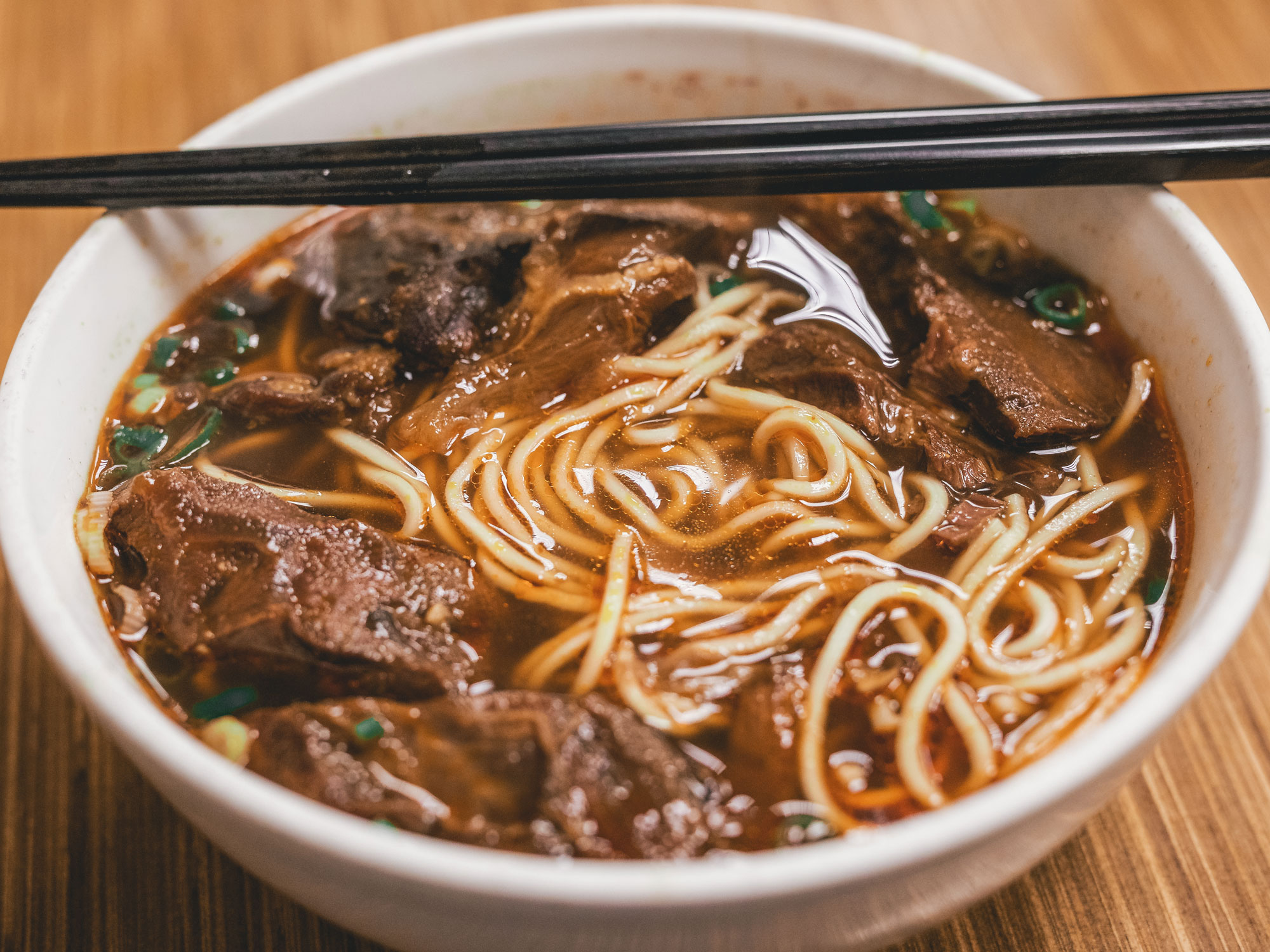 Photo of beef and noodles with chopsticks in a white bowl.