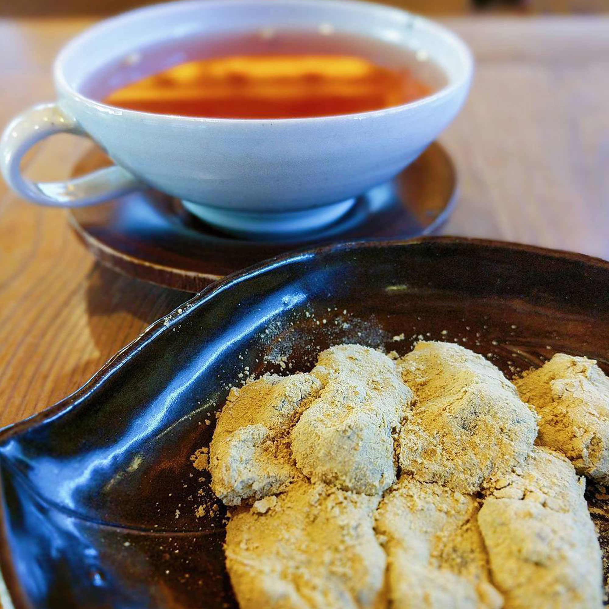 Close up shot of powdered rice cakes and tea in the background.