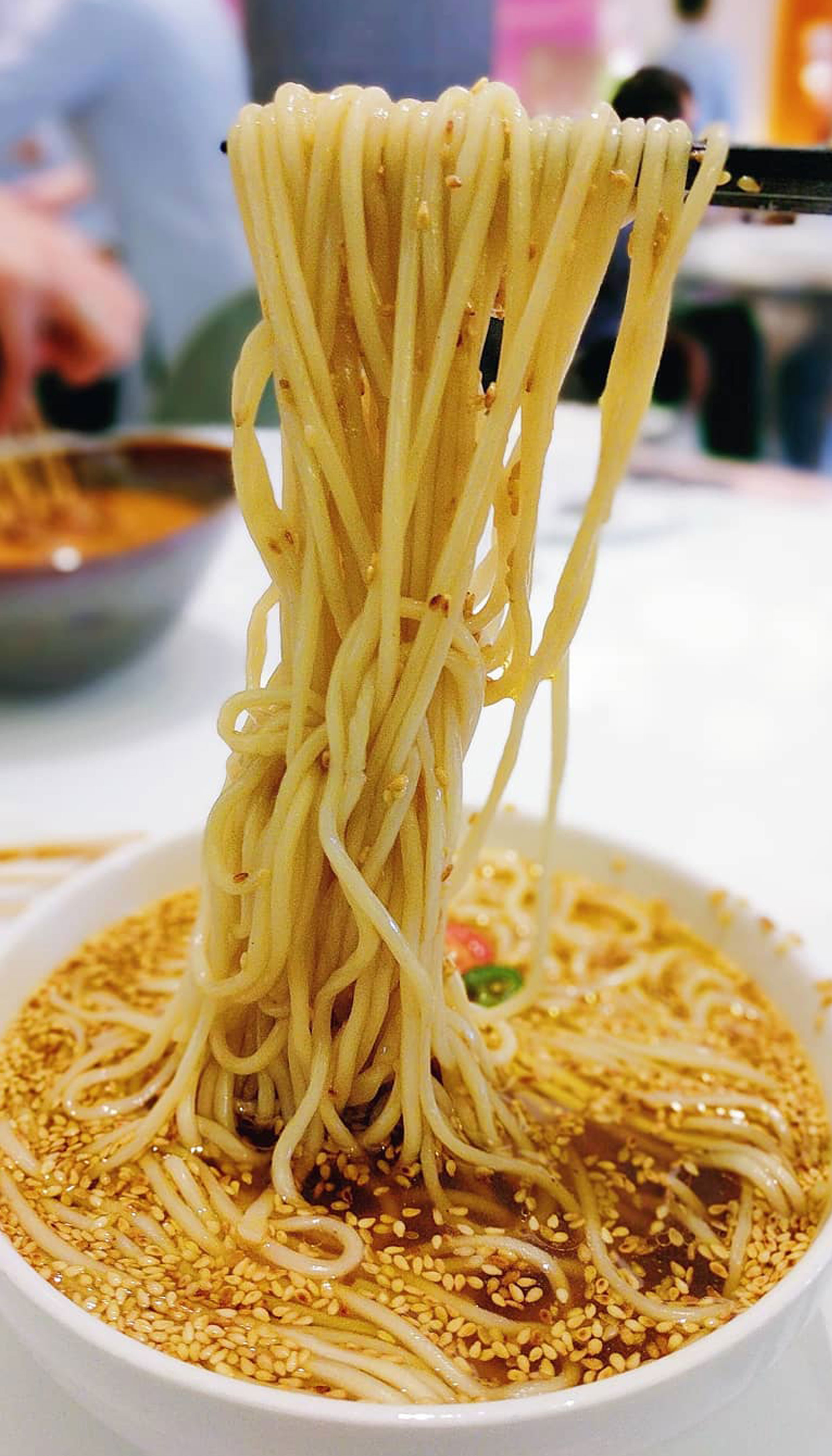 Photo of a noodle soup dish with noodles hanging from chopsticks.