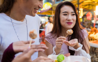 Two friends eating street food in Asia.