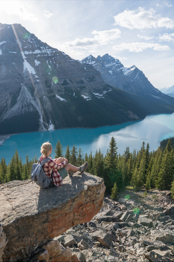Hiking girl reaching mountain top and sits to look at view