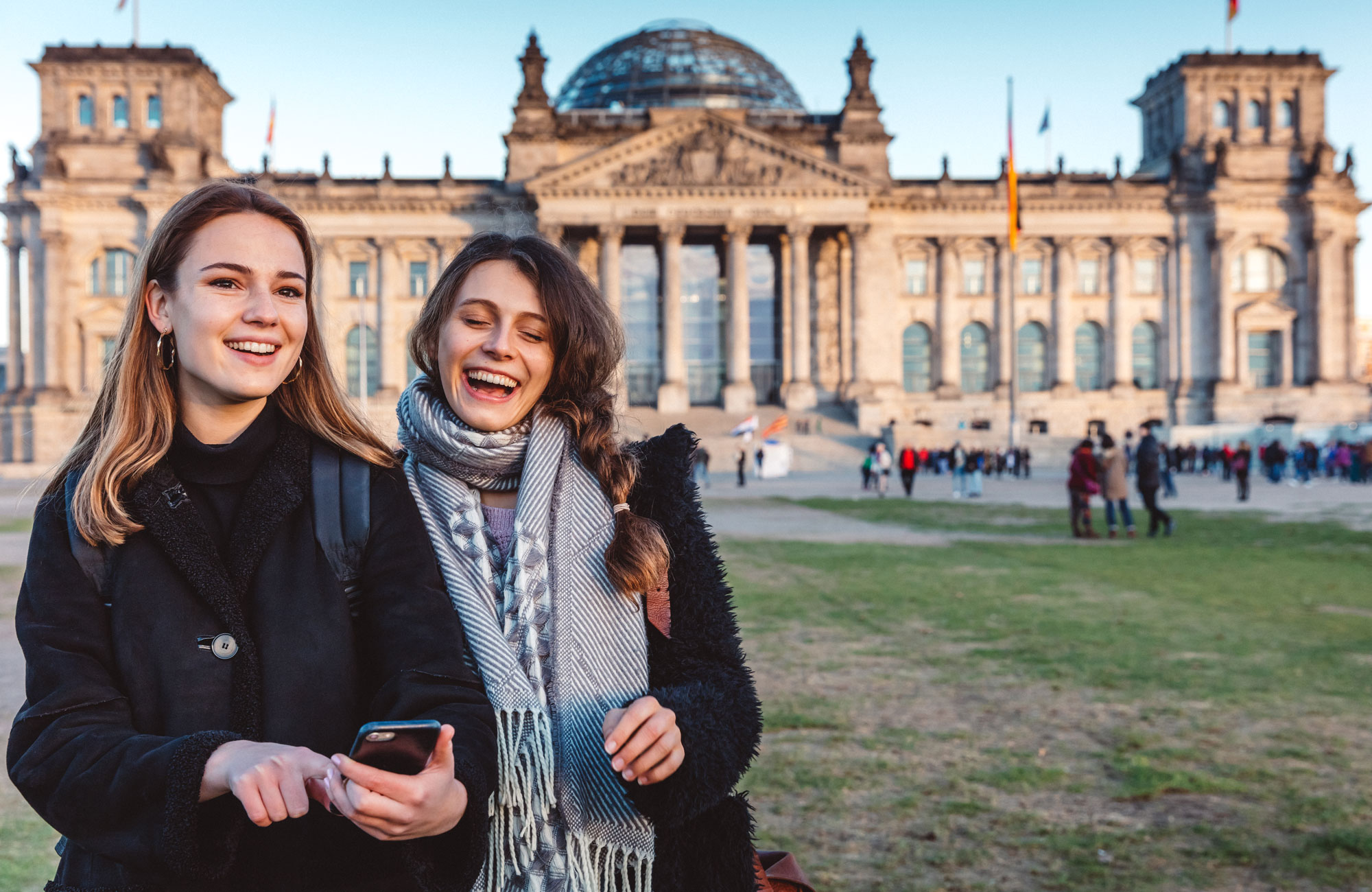 Two friends with mobile phone at The Reichstag in Berlin Berlin, Germany