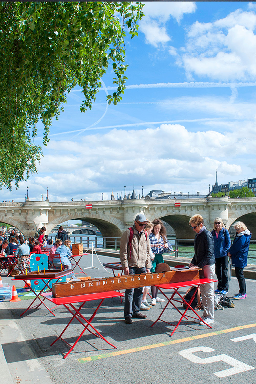 People meeting for play games on the quay along the Seine River in Paris