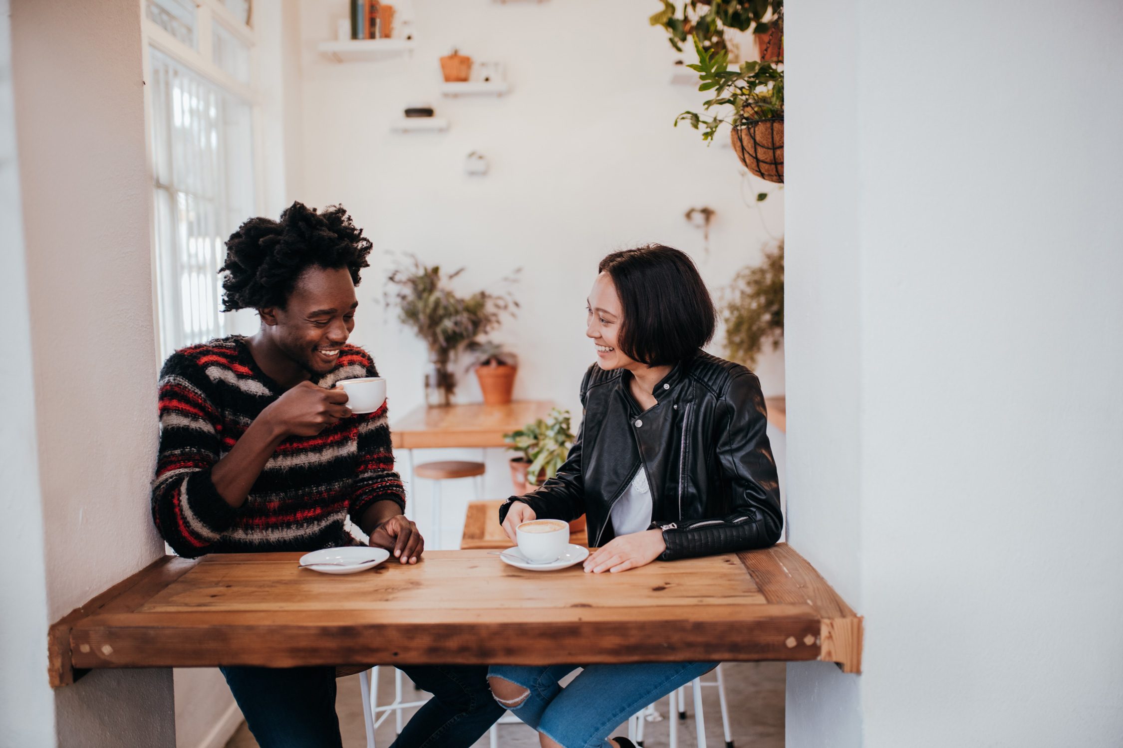 two friends sitting and talking at a cafe