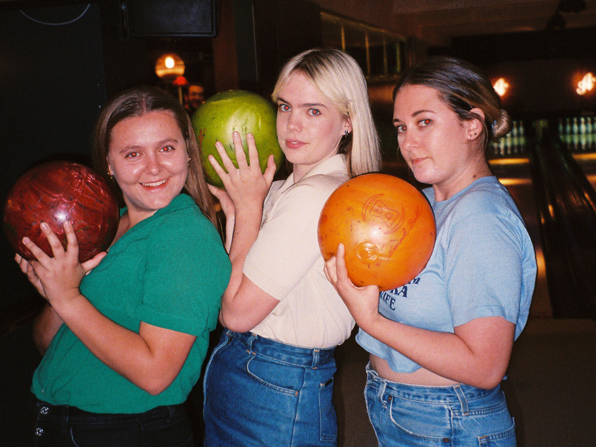 Three friends smiling and holding bowling balls