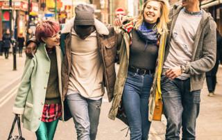 Four friends walking down Brick Lane in London England.