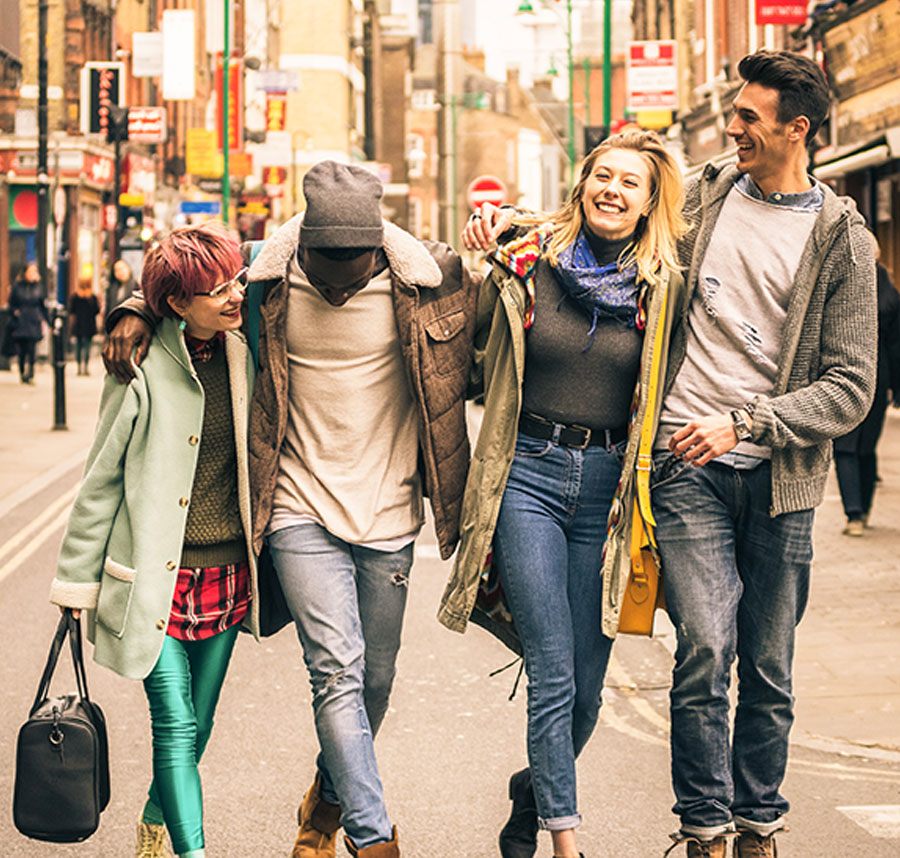 Four friends walking down Brick Lane in London England.