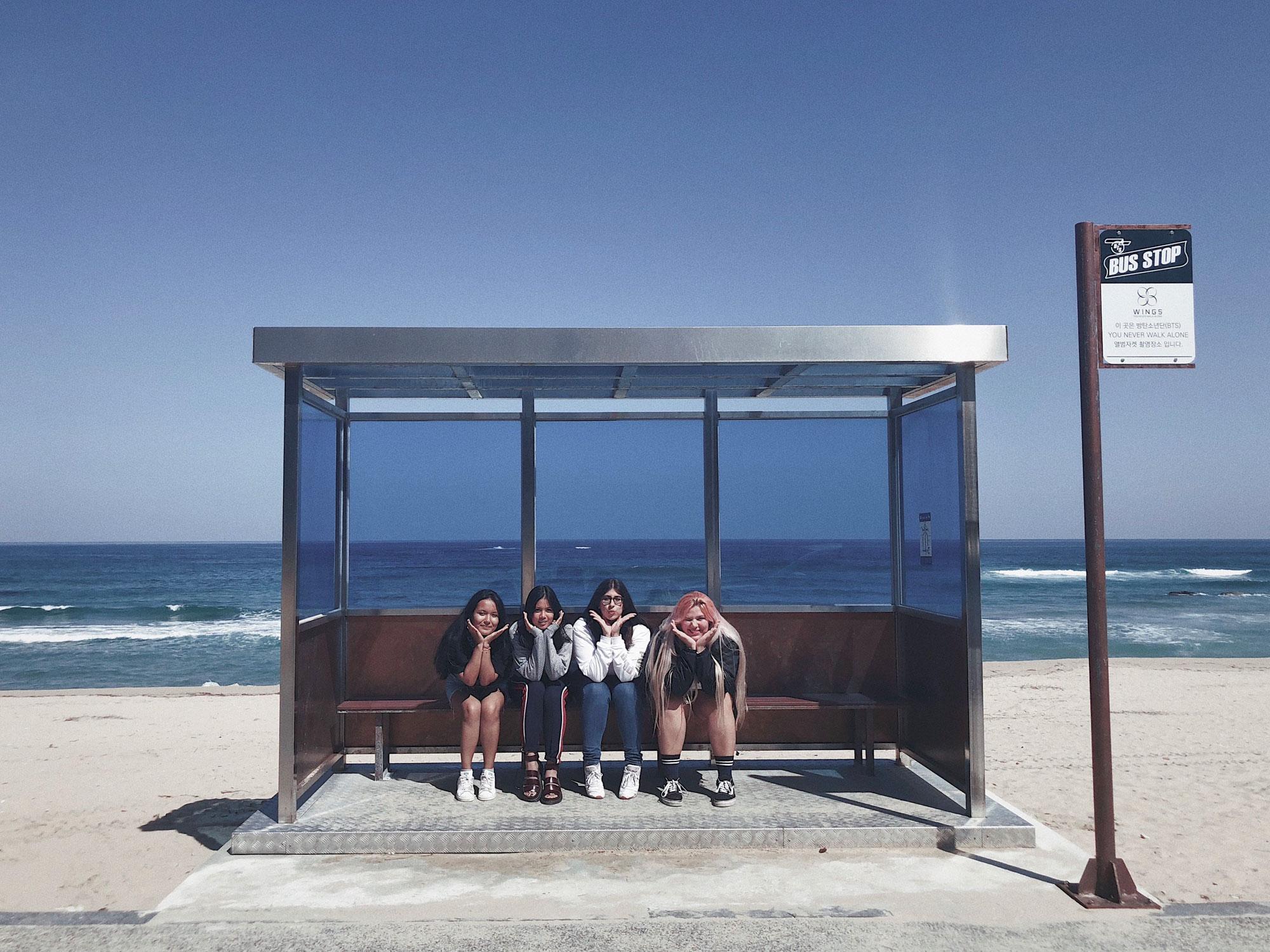 Three students sitting at a bus stop at Jumunji Beach.