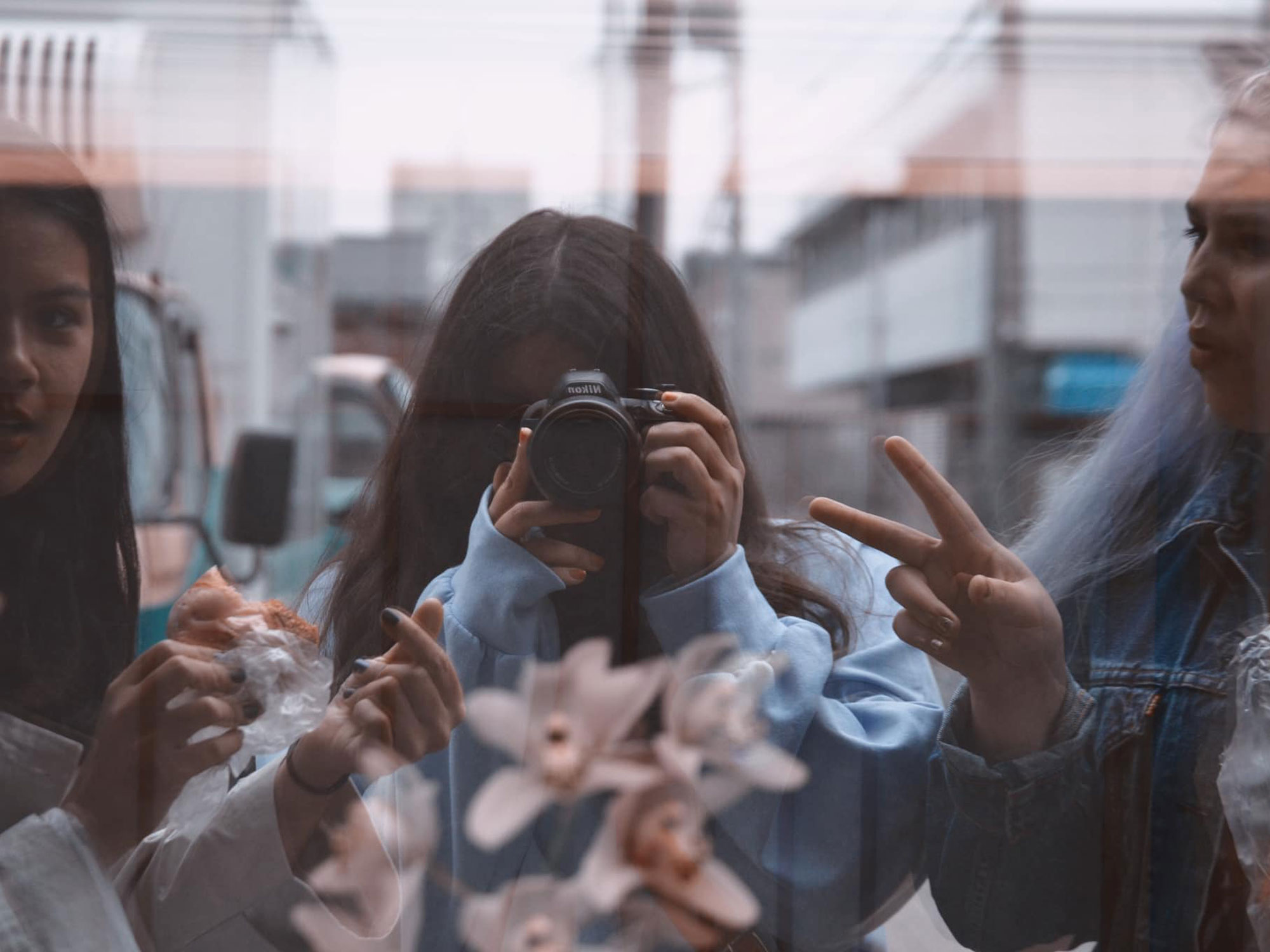 Window reflection with three students.