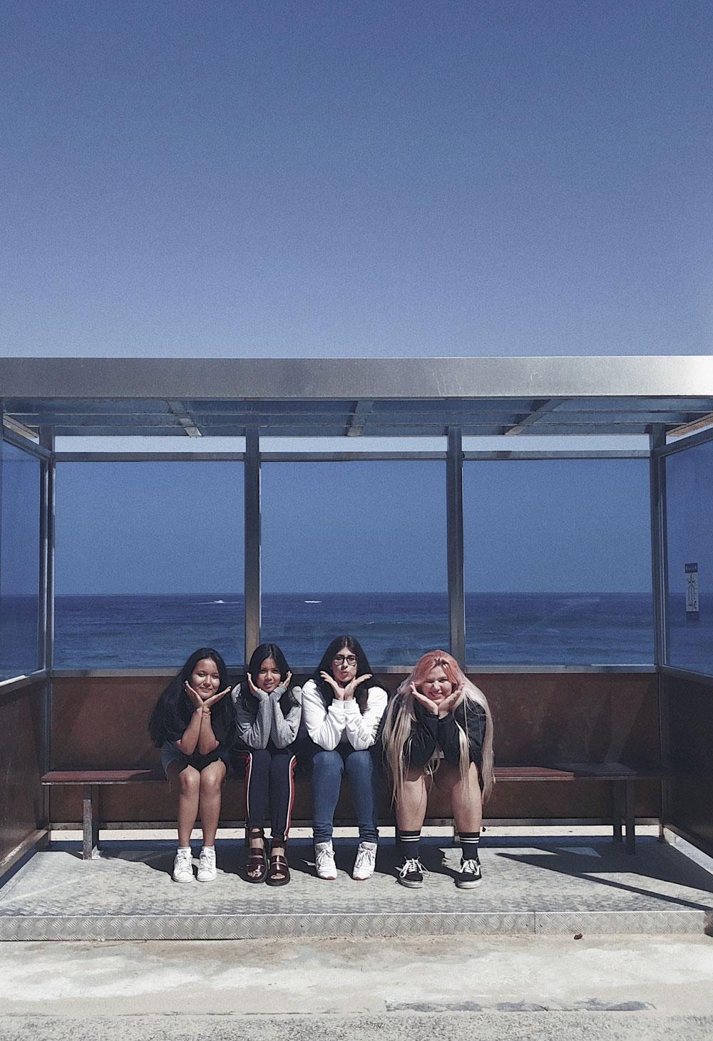 Three students sitting at a bus stop at Jumunjin Beach
