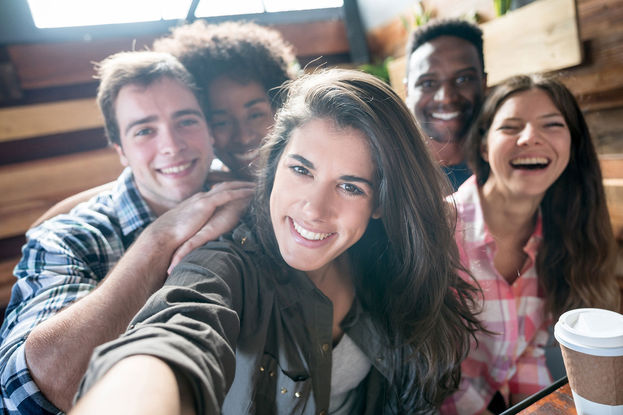 A group of friends take a selfie while grabbing coffee.