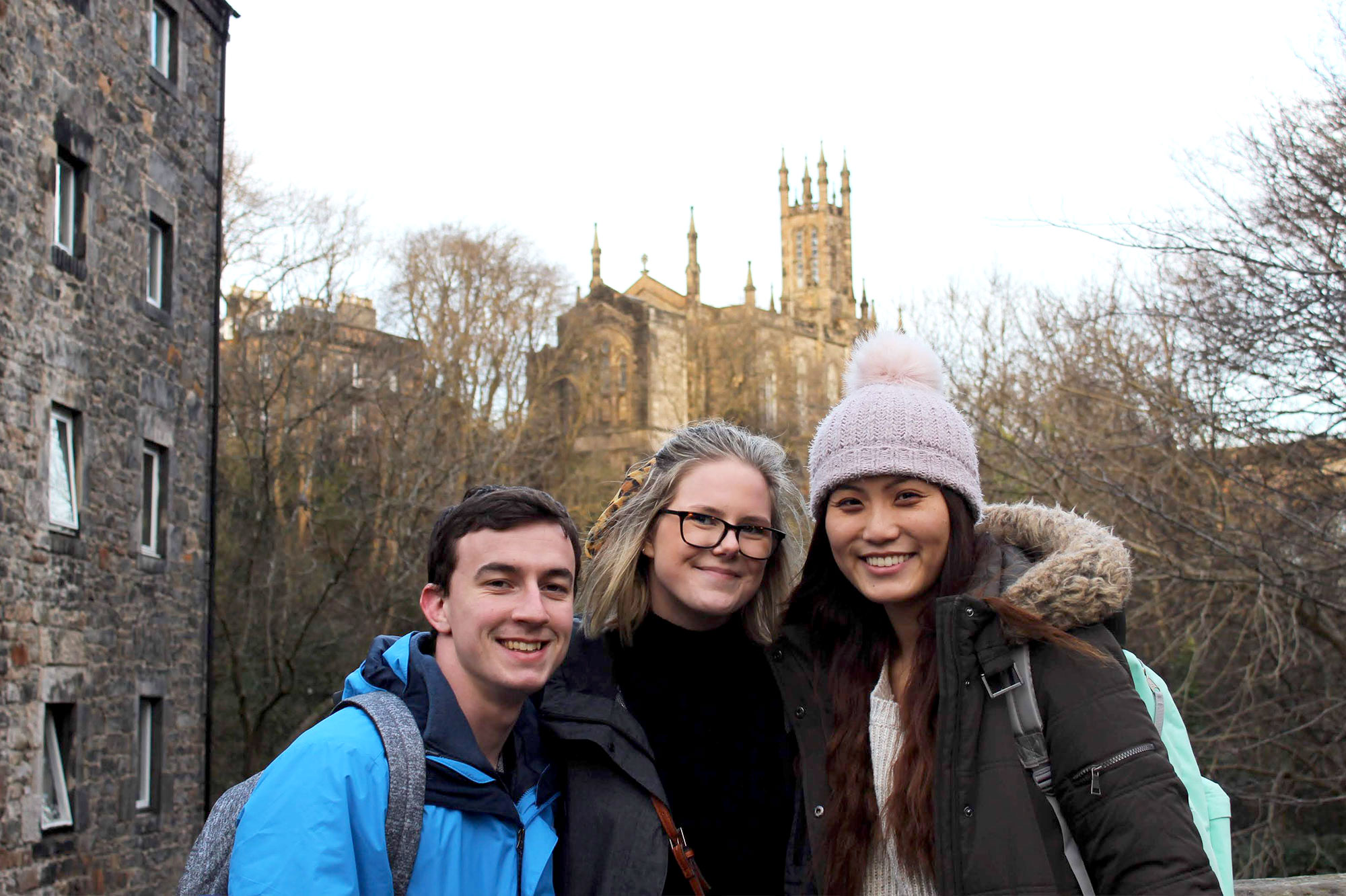Christine Choy smiling at the camera with two friends with stone church and buildings in the background, Glasgow