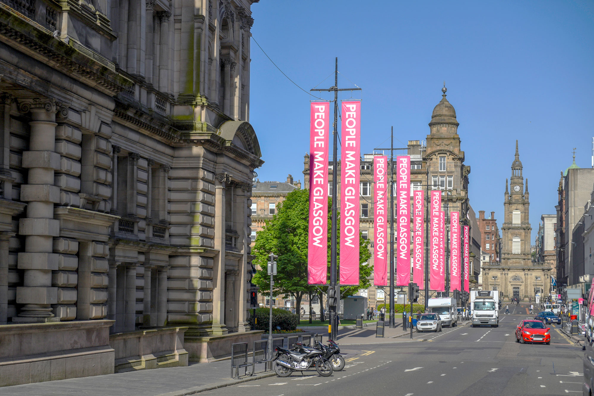 Street view of Glasgow's George Street looking towards George Square and St George's Tron Church (Nelson Mandela Place). with bright pink People Make Glasgow (the city's brand slogan) banners