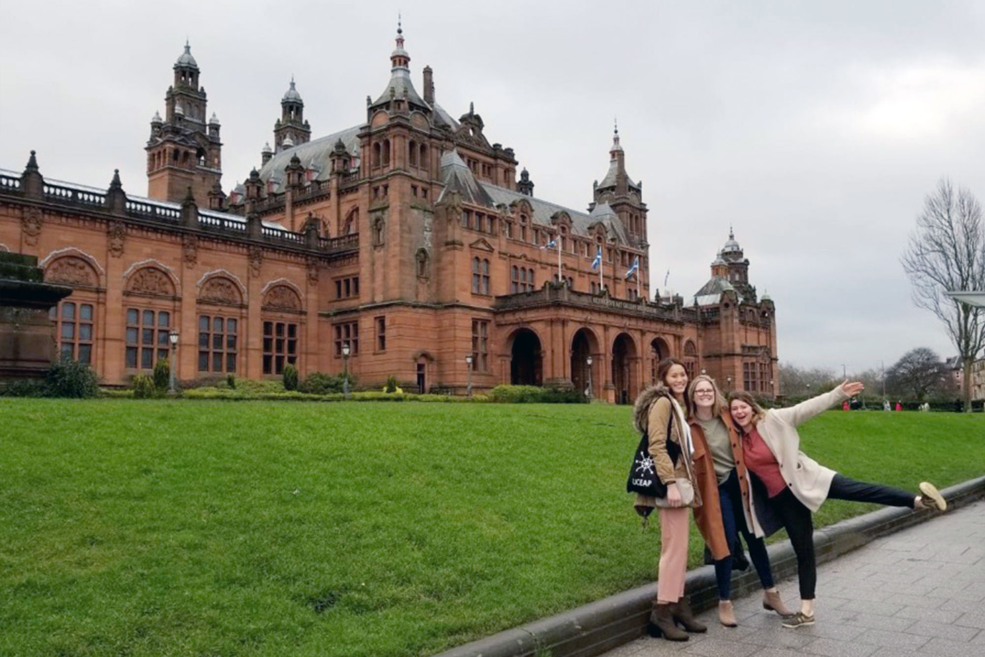 Christine Choy smiling at the camera with two friends in front of the Kelvingrove Museum, Glasgow