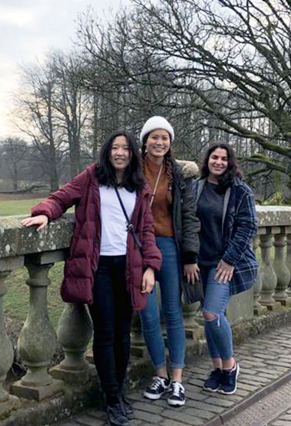 Christine Choy smiling at the camera with two friiends standing on a bridge over a river in parkland, Glasgow