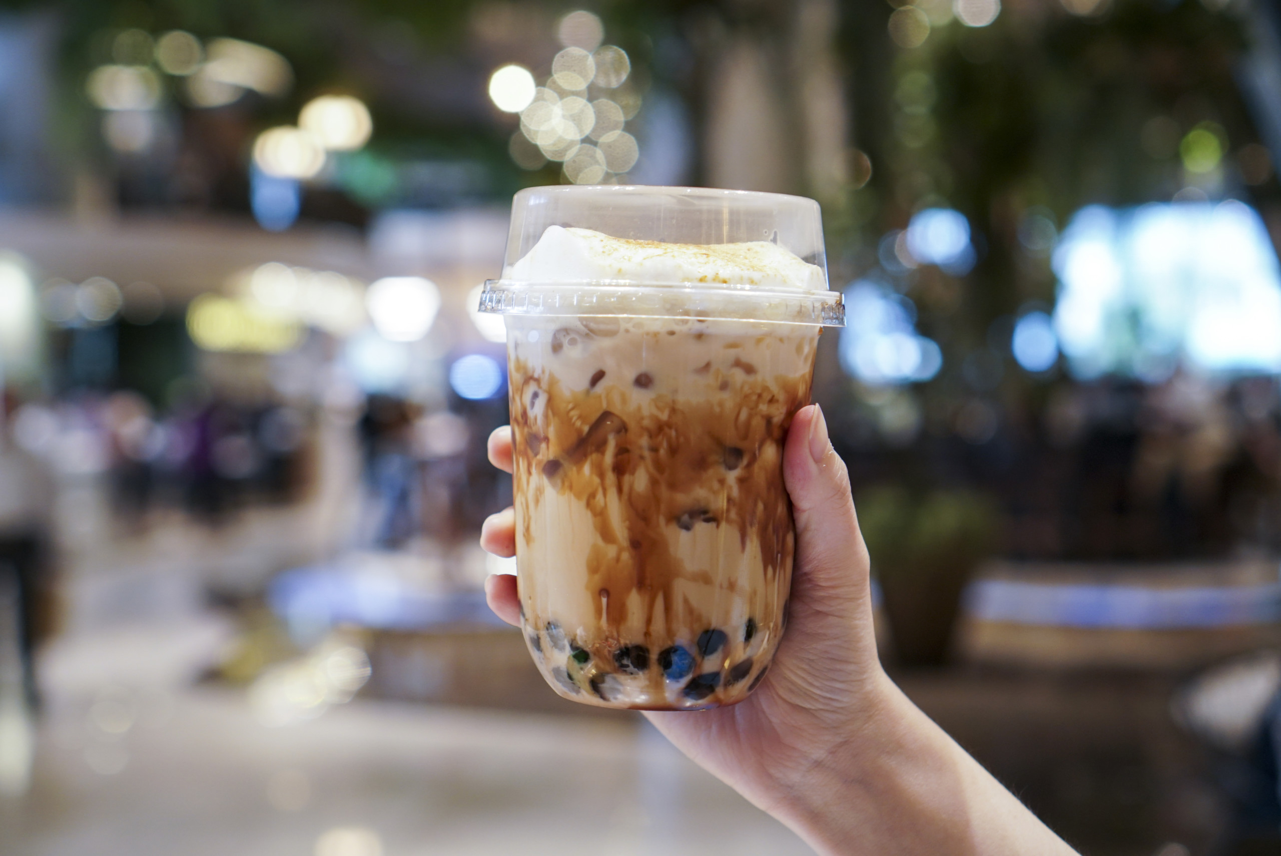 Man holding a plastic cup of bubble/boba milk tea with brown sugar and topped with milk foam.