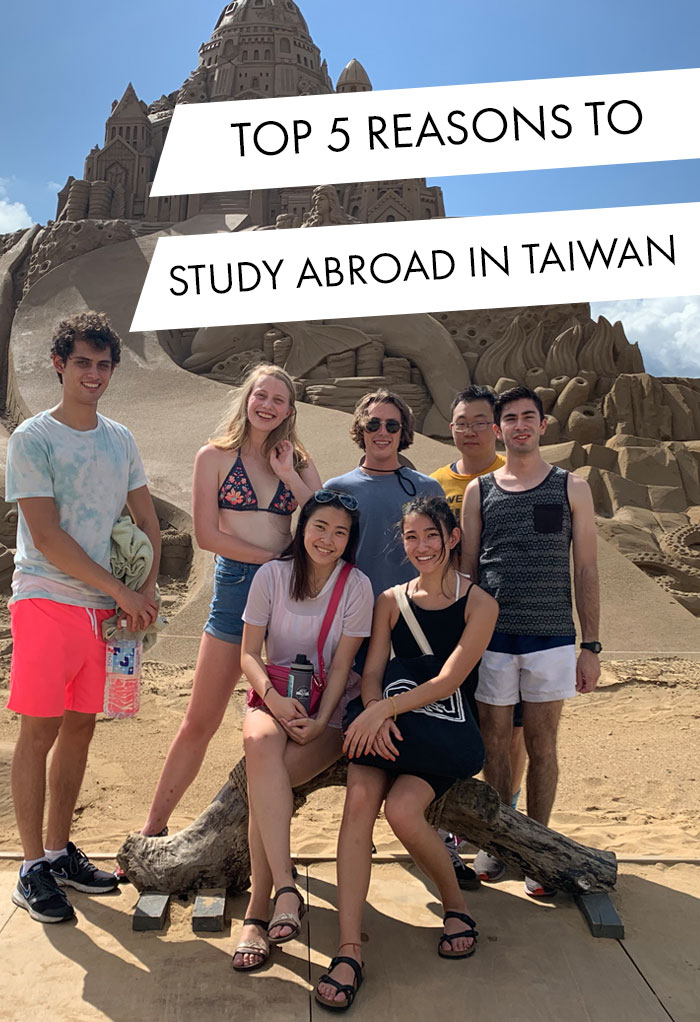 Student from UC Berkeley poses with friends at sand sculpture in Taiwan.