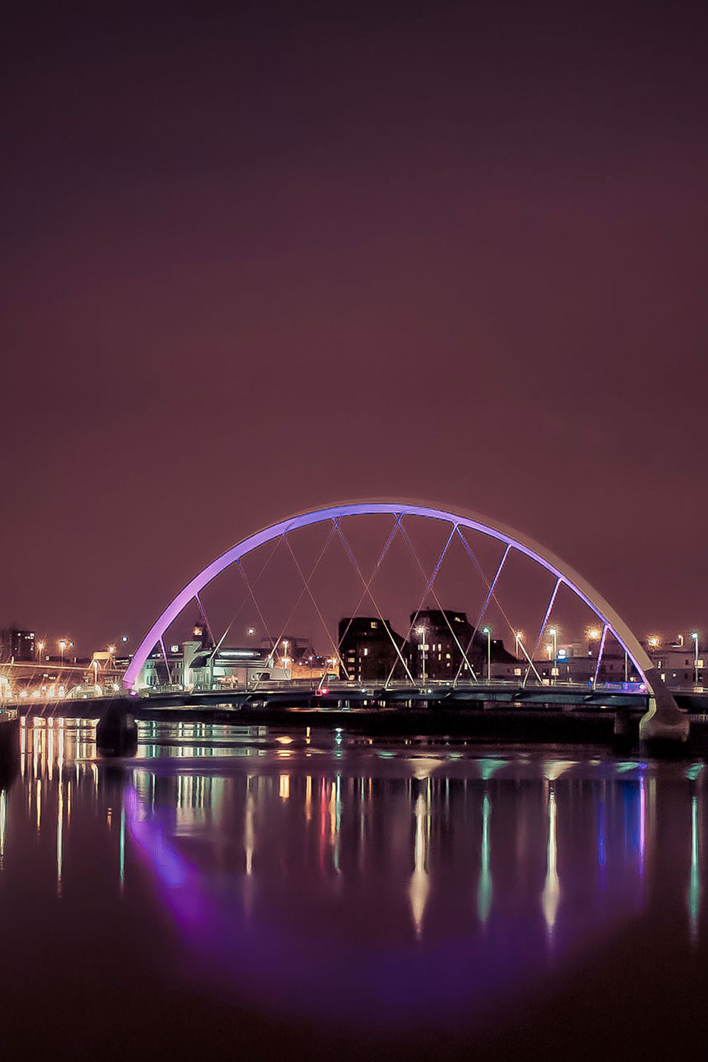 nighttime view of the Clyde Arc with colored lights reflected in the river, in Glasgow.