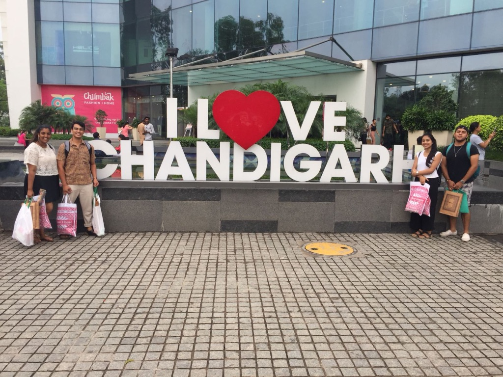 Four students near the 'I love Chandigarh' sign in India