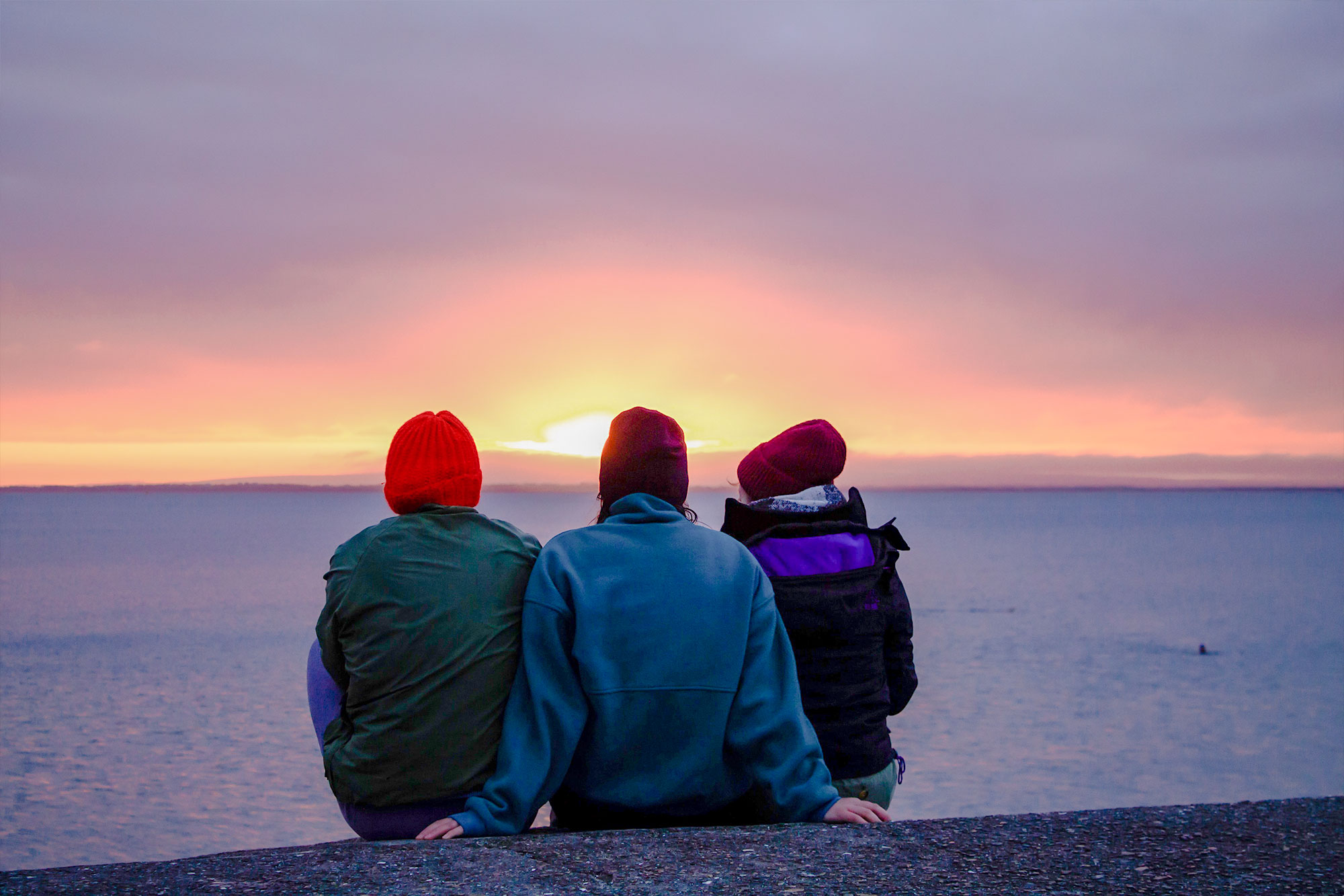 Three friends sitting watching the sunset on the Galway coast, Ireland.