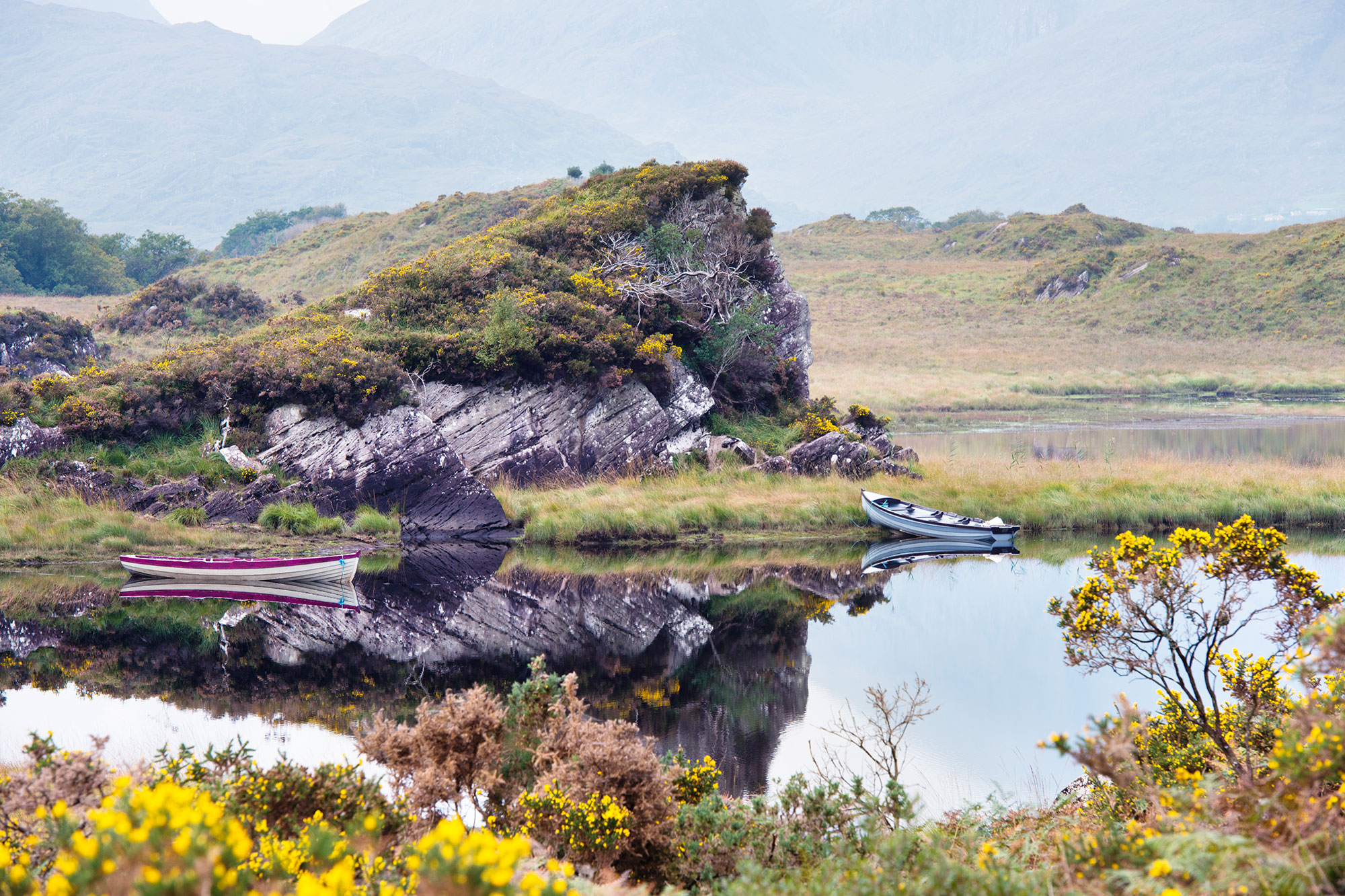 Rugged landscape with boats moored on a lake in Killarney National Park in the south west of Ireland.