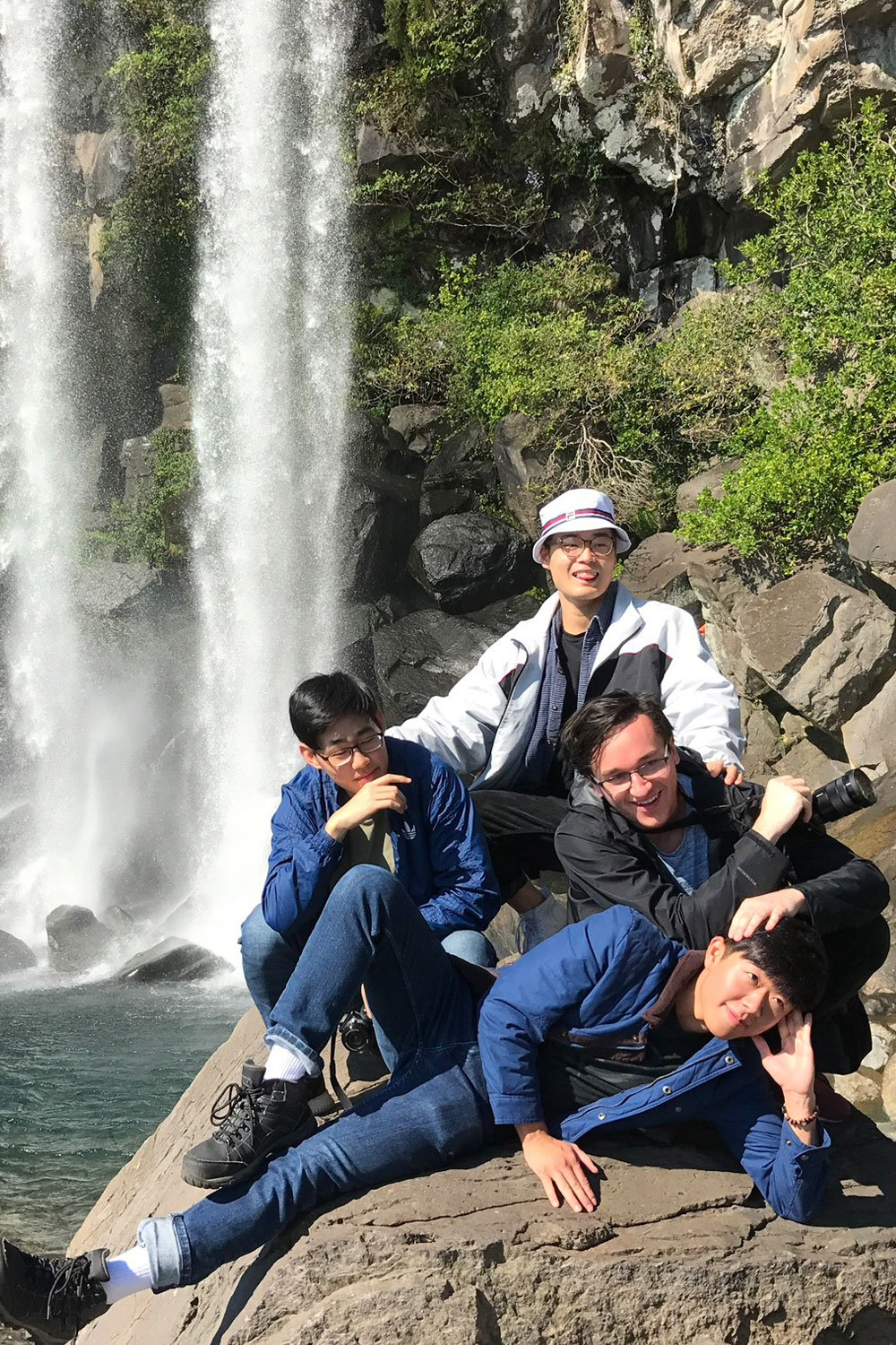 Four friends posing for a photo near a waterfall in Korea.