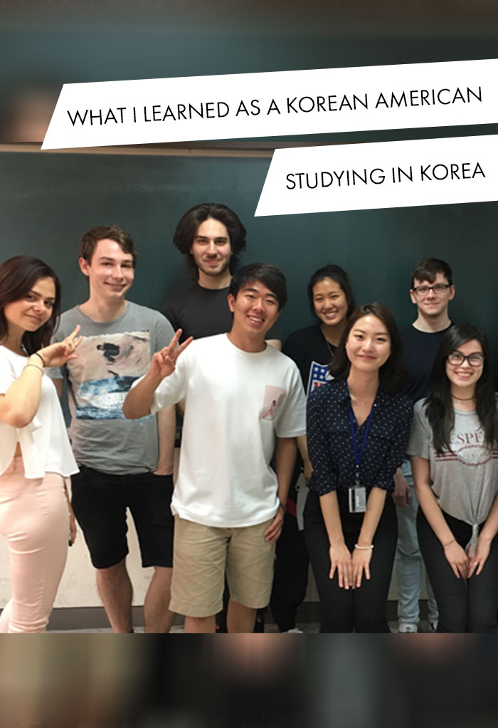 Brandon Yoon poses in front a chalkboard with a group of students.