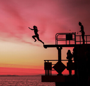 Person jumps off Blackrock Diving Tower at sunset, Galway, Ireland