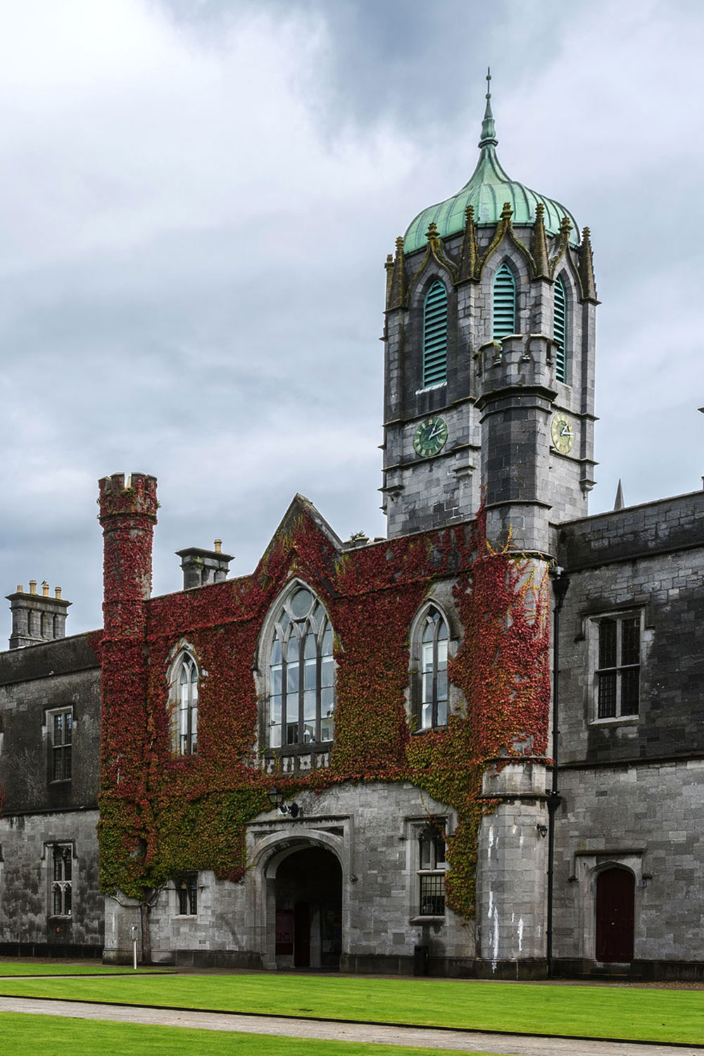Ivy covered clock tower in the historic Quadrangle on National University of Ireland Campus under cloudy sky.