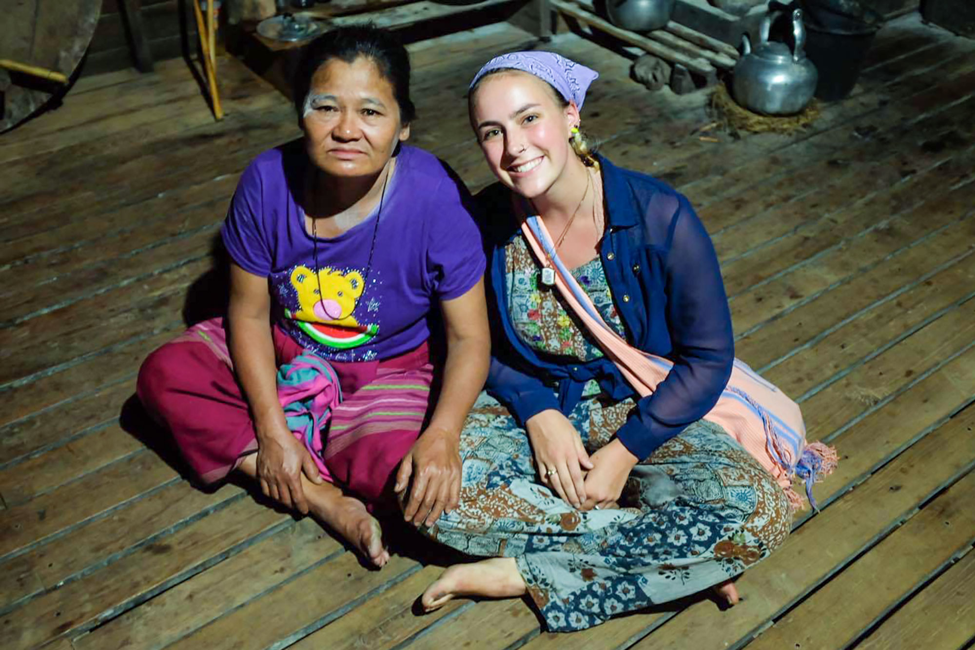 A UCEAP student and an older woman pose for a photo outdoors at night.
