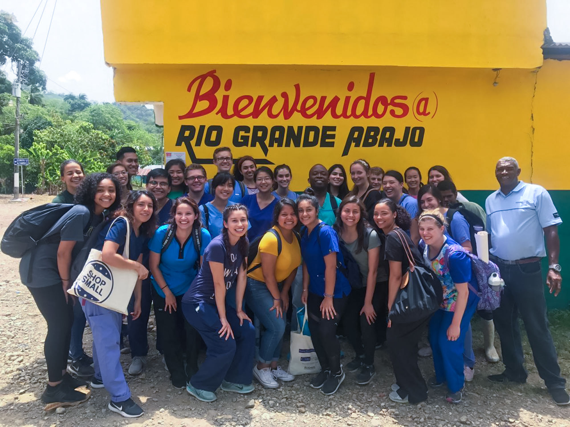 Students pose in front of a welcome sign in the Dominican Republic.