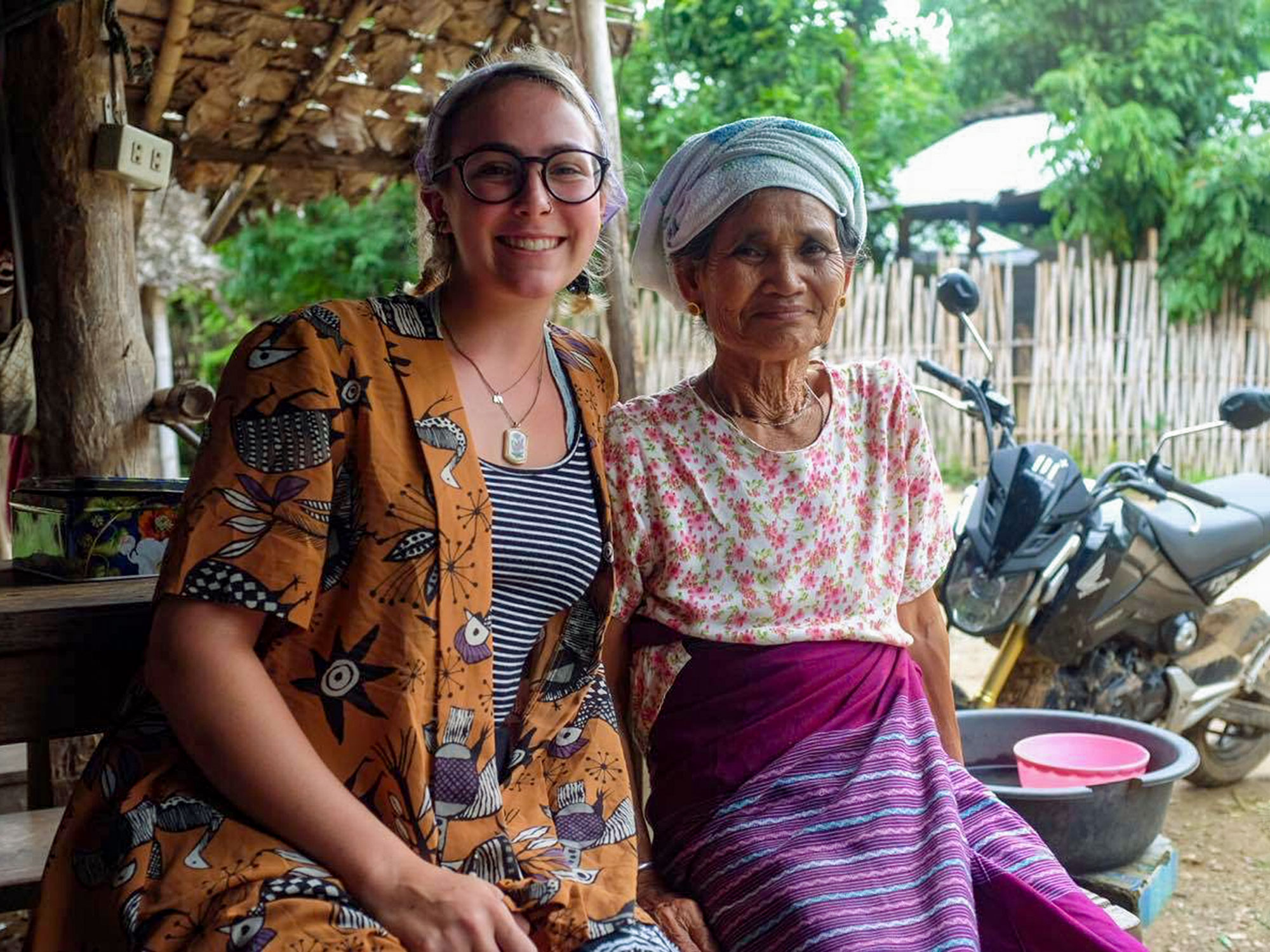UCEAP student and older woman pose on a bench.