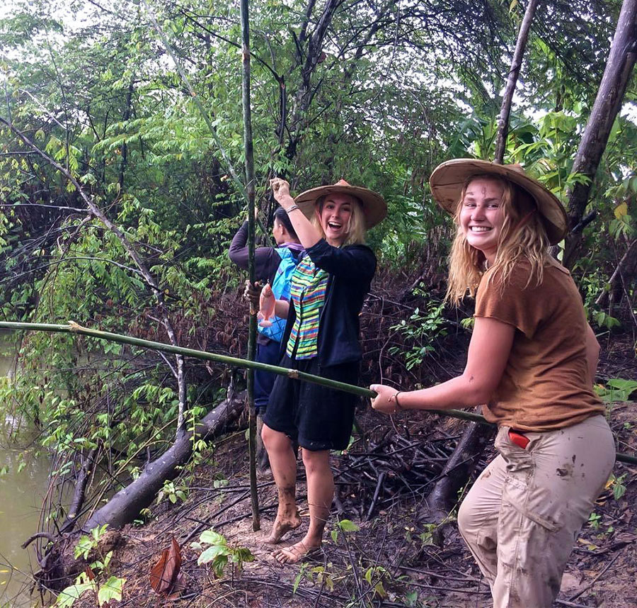 Two students laughing and smiling for camera as stand on a riverbank with bamboo fishing poles.