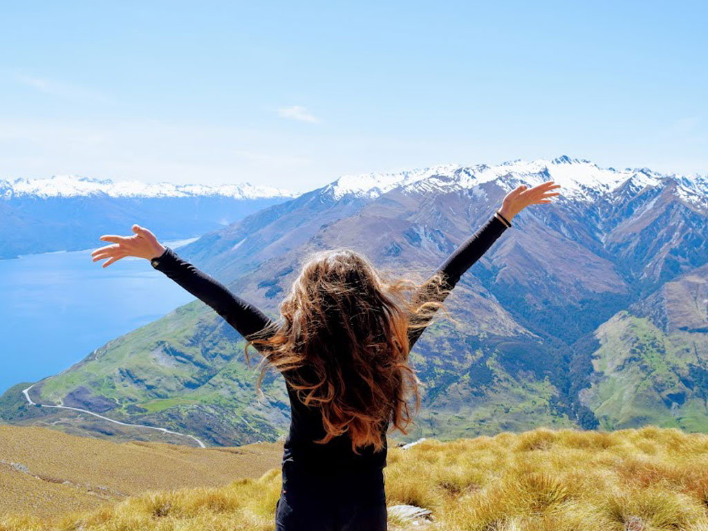 Sierra with her arms in the air and enjoying the view of New Zealand.