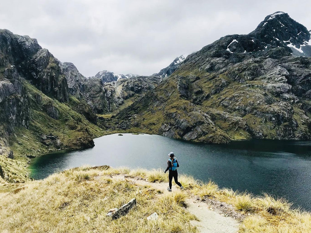 student running down a pathway near a lake and lush green mountains in New Zealand.