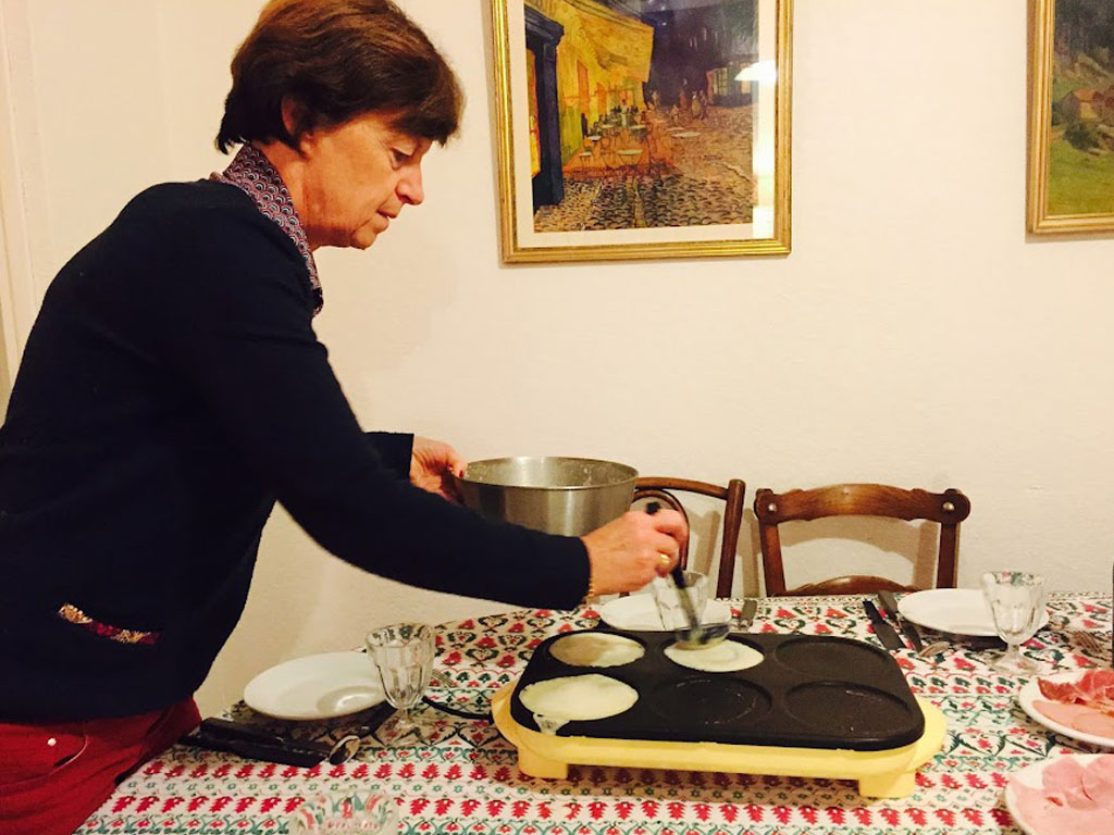 Sierra's host mom flipping crepes at the dining room table in Lyon, France.
