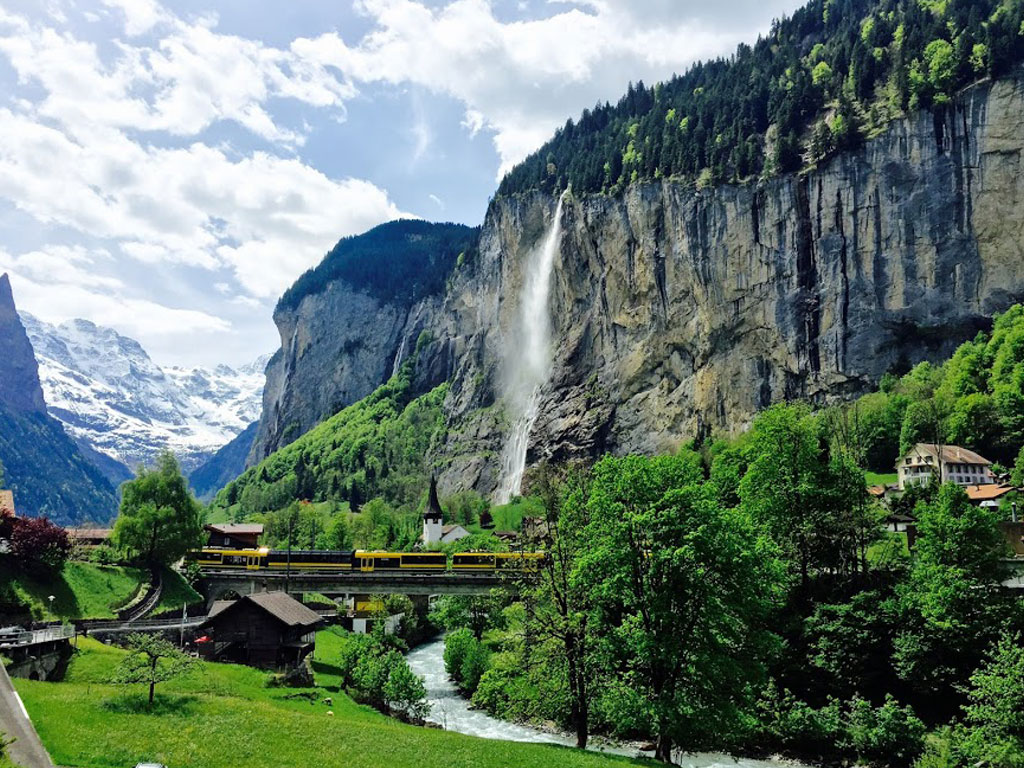 Nature view of a Swiss farm town with a train crossing a river near a mountain.